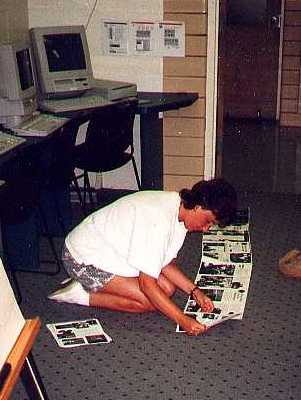 Photograph of a teacher kneeling on the floor, taping photocopied pages together to make a scroll.